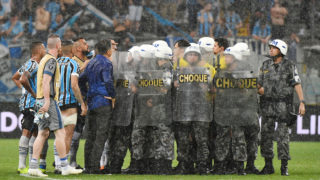 Riot police protect Uruguayan referee Andres Cunha as Brazil's Gremio footballers argue with him after losing their 2018 Copa Libertadores football match against Argentina's River Plate at Gremio Arena, in Porto Alegre, Brazil, on October 30, 2018. - Argentina's River Plate won by 2-1. (Photo by NELSON ALMEIDA / AFP)