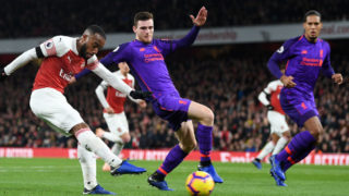 LONDON, ENGLAND - NOVEMBER 03:  Alexandre Lacazette of Arsenal shoots past Andy Robertson of Liverpool as Virgil van Dijk of Liverpool looks on during the Premier League match between Arsenal FC and Liverpool FC at Emirates Stadium on November 3, 2018 in London, United Kingdom.  (Photo by Michael Regan/Getty Images)