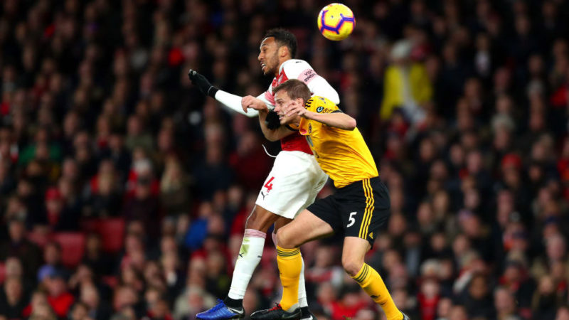 LONDON, ENGLAND - NOVEMBER 11: Pierre-Emerick Aubameyang of Arsenal wins a header over Ryan Bennett of Wolverhampton Wanderers during the Premier League match between Arsenal FC and Wolverhampton Wanderers at Emirates Stadium on November 11, 2018 in London, United Kingdom.  (Photo by Clive Rose/Getty Images)