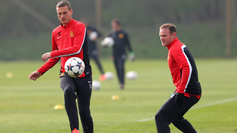 MANCHESTER, ENGLAND - MARCH 31:  Nemanja Vidic of Manchester United passes the ball past Wayne Rooney during a training session at the Aon Training Complex on March 31, 2014 in Manchester, England.  (Photo by Alex Livesey/Getty Images)