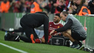 Liverpool's English midfielder Alex Oxlade-Chamberlain (C) picks up an injury during the UEFA Champions League first leg semi-final football match between Liverpool and Roma at Anfield stadium in Liverpool, north west England on April 24, 2018. (Photo by Oli SCARFF / AFP)