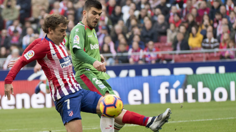 Atletico Madrid's French forward Antoine Griezmann (L) vies with Alaves´ Spanish defender Martin Aguirregabiria during the Spanish league football match between Club Atletico de Madrid and Deportivo Alaves at the Wanda Metropolitano stadium in Madrid on December 8, 2018. (Photo by CURTO DE LA TORRE / AFP)