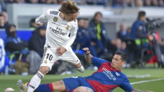 Real Madrid's Croatian midfielder Luka Modric (L) vies for the ball with Huesca's Argentinian forward Chimy Avila (R) during the Spanish league football match between SD Huesca and Real Madrid CF at the El Alcoraz stadium in Huesca, on December 9, 2018. (Photo by ANDER GILLENEA / AFP)