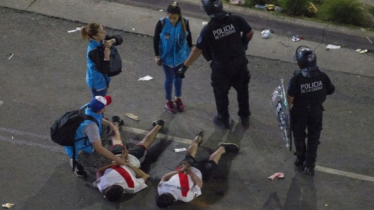 Fans of River Plate are detained by riot police at the Plaza de la Republica in Buenos Aires, Argentina after the team won the all-Argentine Copa Libertadores final against Boca Juniors at the Santiago Bernabeu stadium in Madrid, Spain on December 9, 2018. (Photo by ALBERTO RAGGIO / AFP)
