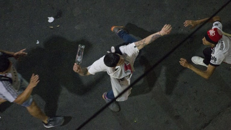 In the early morning a River Plate fan throws a bottle to the riot police at the Plaza de la Republica in Buenos Aires, Argentina after the team won the all-Argentine Copa Libertadores final against Boca Juniors at the Santiago Bernabeu stadium in Madrid, Spain on December 10, 2018. (Photo by ALBERTO RAGGIO / AFP)