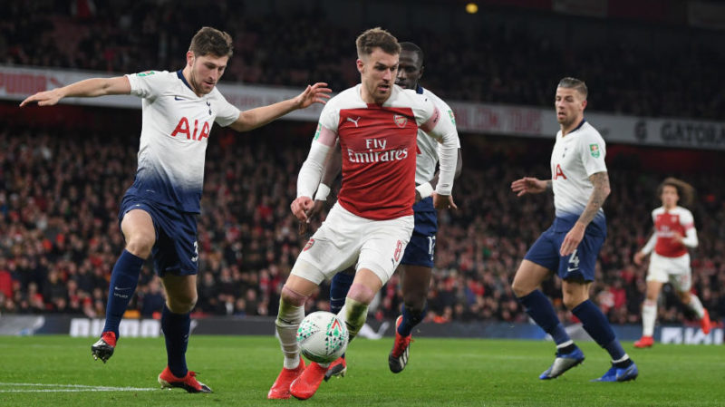 LONDON, ENGLAND - DECEMBER 19:  Aaron Ramsey of Arsenal and Ben Davies of Tottenham Hotspur challenge for the ball during the Carabao Cup Quarter Final match between Arsenal and Tottenham Hotspurat Emirates Stadium on December 19, 2018 in London, United Kingdom. (Photo by Shaun Botterill/Getty Images)