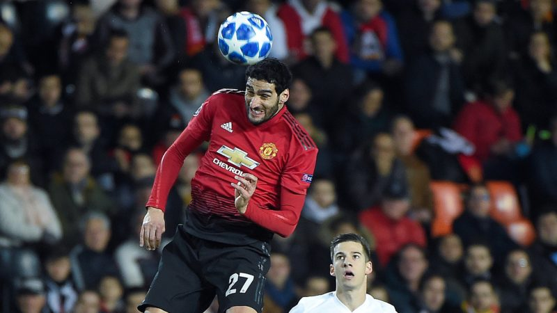 Manchester United's Belgian midfielder Marouane Fellaini (L) heads the ball next to Valencia's Spanish forward Santi Mina during the UEFA Champions League group H football match between Valencia CF and Manchester United at the Mestalla stadium in Valencia on December 12, 2018. (Photo by JOSE JORDAN / AFP)
