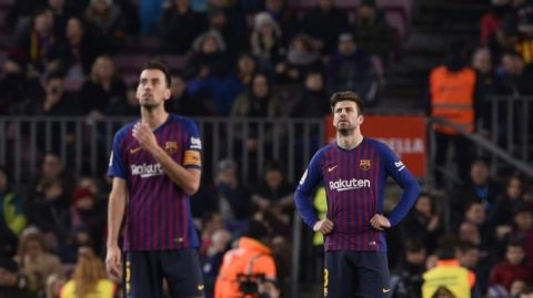 Barcelona's Spanish midfielder Sergio Busquets (L) and Barcelona's Spanish defender Gerard Pique react during the Spanish League football match between Barcelona and Leganes at the Camp Nou stadium in Barcelona on January 20, 2019. (Photo by Josep LAGO / AFP)