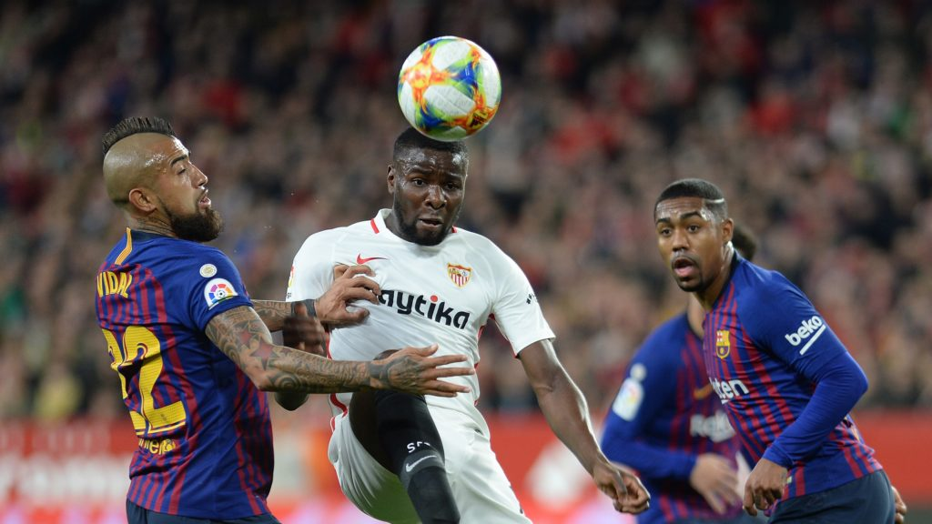 Sevilla's French defender Ibrahim Amadou (C) vies with Barcelona's Chilean midfielder Arturo Vidal (L) and Barcelona's Brazilian midfielder Malcom during the Spanish Copa del Rey (King's Cup) quarter-final first leg football match between Sevilla FC and FC Barcelona at the Ramon Sanchez Pizjuan stadium in Seville on January 23, 2019. (Photo by CRISTINA QUICLER / AFP)