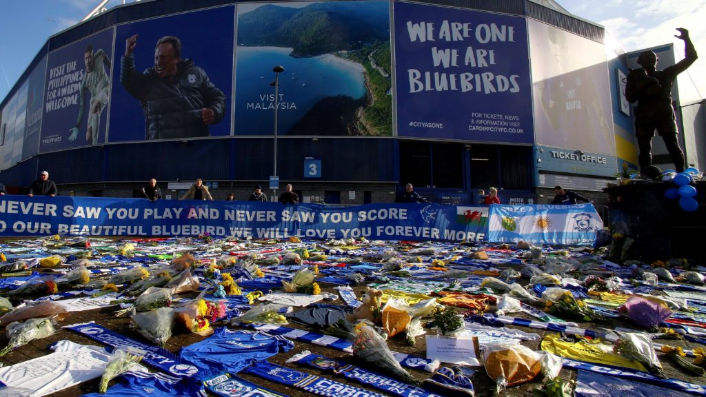 """Cardiff City scarves and jerseys, flowers, messages and other tributes to the football club's new signing Emiliano Sala, whose flight disappeared from radar over the English Channel north of Guernsey, are seen outside the Cardiff City Stadium in Cardiff, south Wales on January 25, 2019. - British investigators said on January 25 they were probing the licence held by the pilot of the small plane carrying Premier League player Emiliano Sala that went missing over the Channel this week. Police on January 24 ended their search for Sala, saying the chances of finding the Argentinian alive three days after his small plane went missing were """"extremely remote"""". The light aircraft transporting the 28-year-old striker, who signed for Cardiff City at the weekend, disappeared from radar around 20 kilometres (12 miles) north of Guernsey on the night of January 21. (Photo by GEOFF CADDICK / AFP)"""