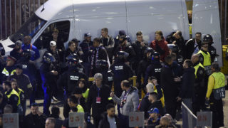 A group of Lyon fans are held by police before the UEFA Champions League round of 16, second leg football match between FC Barcelona and Olympique Lyonnais at the Camp Nou stadium in Barcelona on March 13, 2019. (Photo by Josep LAGO / AFP)