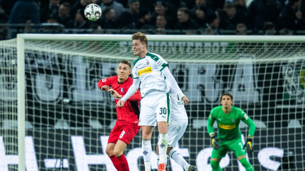 15 March 2019, North Rhine-Westphalia, Mönchengladbach: Soccer: Bundesliga, Borussia Mönchengladbach - SC Freiburg, 26th matchday in Borussia Park. Gladbach's Nico Elvedi (M) beheads the ball. Freiburg's Mike Frantz is trying to defend. Photo: Marcel Kusch/dpa - IMPORTANT NOTE: In accordance with the requirements of the DFL Deutsche Fußball Liga or the DFB Deutscher Fußball-Bund, it is prohibited to use or have used photographs taken in the stadium and/or the match in the form of sequence images and/or video-like photo sequences.