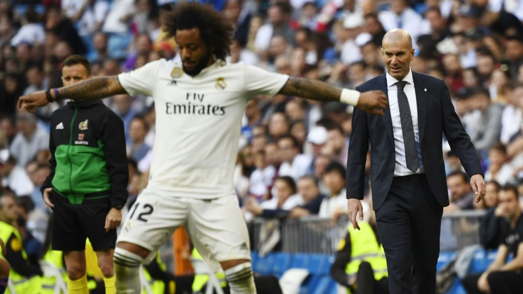 Real Madrid's French coach Zinedine Zidane (R) looks at Real Madrid's Brazilian defender Marcelo controlling the ball during the Spanish league football match between Real Madrid CF and RC Celta de Vigo at the Santiago Bernabeu stadium in Madrid on March 16, 2019. (Photo by GABRIEL BOUYS / AFP)