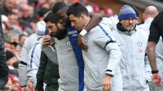 Chelsea's German defender Antonio Rudiger (C) is helped off after picking up an injury during the English Premier League football match between Liverpool and Chelsea at Anfield in Liverpool, north west England on April 14, 2019. (Photo by Paul ELLIS / AFP) / RESTRICTED TO EDITORIAL USE. No use with unauthorized audio, video, data, fixture lists, club/league logos or 'live' services. Online in-match use limited to 120 images. An additional 40 images may be used in extra time. No video emulation. Social media in-match use limited to 120 images. An additional 40 images may be used in extra time. No use in betting publications, games or single club/league/player publications. /