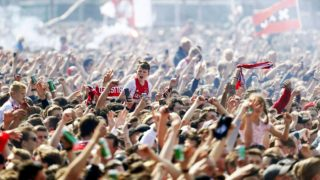 Ajax Amsterdam football supporters celebrate their club's 34th national champion title after winnning the 2019 Dutch Eredivisie championship outside the Museumplein in Amsterdam on May 16, 2019. (Photo by Robin van Lonkhuijsen / ANP / AFP) / Netherlands OUT