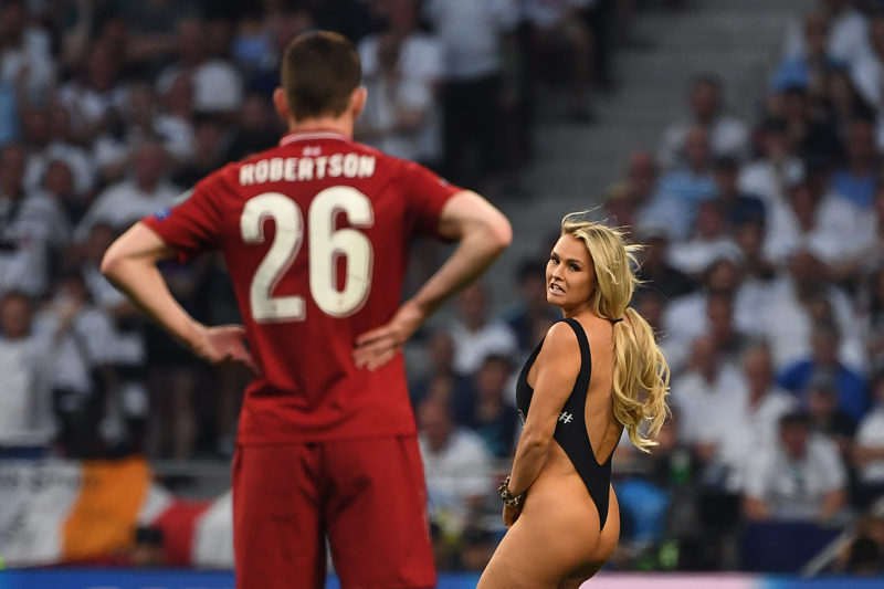 Liverpool's Scottish defender Andrew Robertson looks at a pitch-invader running on the pitch during the UEFA Champions League final football match between Liverpool and Tottenham Hotspur at the Wanda Metropolitano Stadium in Madrid on June 1, 2019. (Photo by Paul ELLIS / AFP)