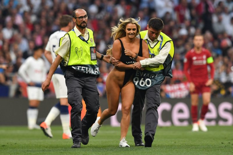 EDITORS NOTE: Graphic content / Security escort a pitch invader during the UEFA Champions League final football match between Liverpool and Tottenham Hotspur at the Wanda Metropolitan Stadium in Madrid on June 1, 2019. (Photo by Ben STANSALL / AFP)