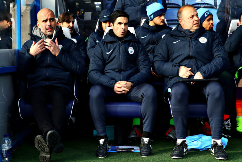 HUDDERSFIELD, ENGLAND - JANUARY 20: Manchester City manager Josep Guardiola (L) looks on from the sidelines with assistants Mikel Arteta (centre) and Rodolfo Burrell (R) during the Premier League match between Huddersfield Town and Manchester City at John Smith's Stadium on January 20, 2019 in Huddersfield, United Kingdom. (Photo by Chris Brunskill/Fantasista/Getty Images)