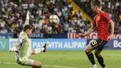 Spain's forward Dani Olmo (R) scores his team's second goal past Germany's goalkeeper Alexander Nuebel during the final match of the UEFA U21 European Football Championships between Spain and Germany on June 30, 2019 at the Friuli stadium in Udine. (Photo by Miguel MEDINA / AFP)