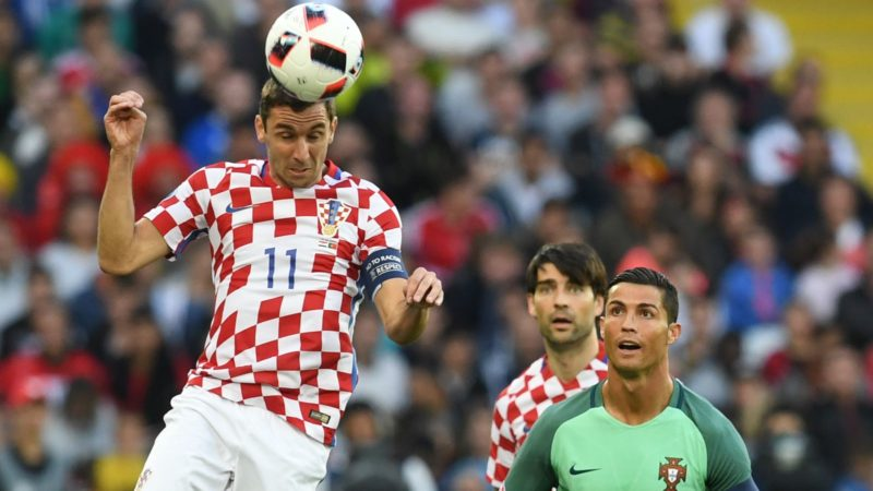 Croatia's defender Darijo Srna (L) heads the ball next to Portugal's forward Cristiano Ronaldo (R) during the round of sixteen football match Croatia against Portugal of the Euro 2016 football tournament, on June 25, 2016 at the Bollaert-Delelis stadium in Lens. (Photo by FRANCISCO LEONG / AFP)