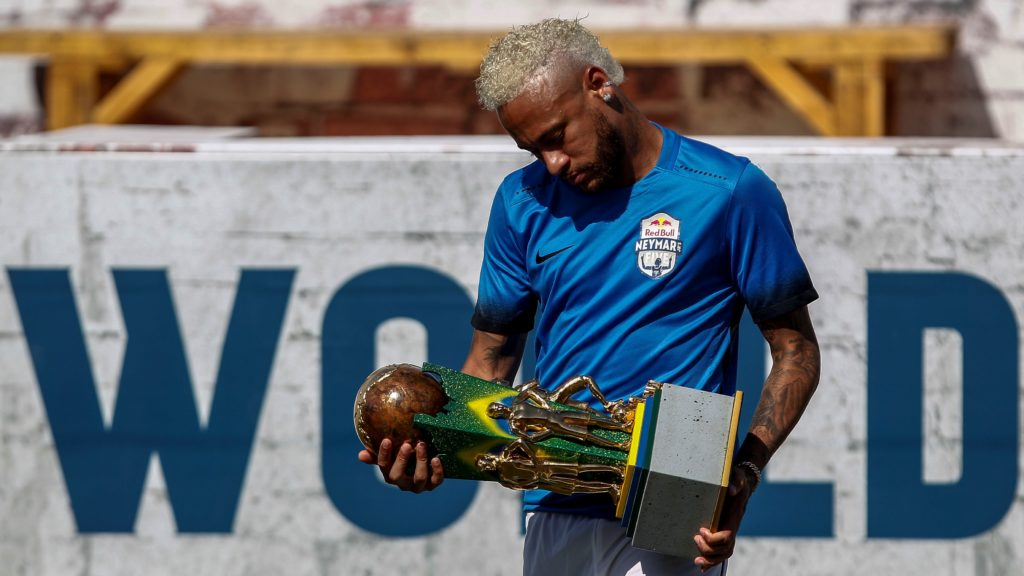 Brazilian football star Neymar holds a trophy during a five-a-side football tournament for his charity Neymar Junior Project Institute, in Praia Grande, Sao Paulo, Brazil, on July 13, 2019. (Photo by Miguel SCHINCARIOL / AFP)
