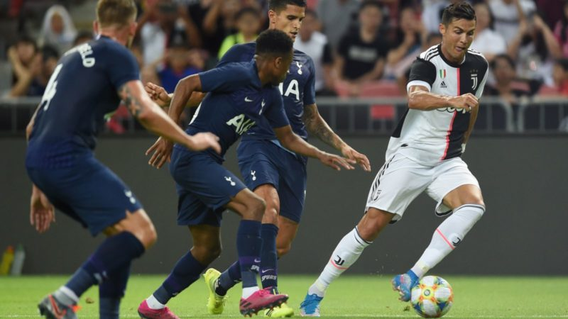 Juventus' Cristiano Ronaldo (R) runs with the ball past Tottenham Hotspur players during the International Champions Cup football match between Juventus and Tottenham Hotspur in Singapore on July 21, 2019. (Photo by Roslan RAHMAN / AFP)