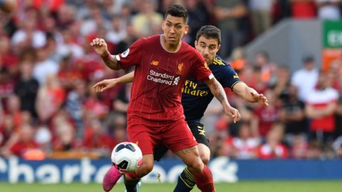 Liverpool's Brazilian midfielder Roberto Firmino (L) vies with Arsenal's Greek defender Sokratis Papastathopoulos (R) during the English Premier League football match between Liverpool and Arsenal at Anfield in Liverpool, north west England on August 24, 2019. (Photo by Ben STANSALL / AFP) / RESTRICTED TO EDITORIAL USE. No use with unauthorized audio, video, data, fixture lists, club/league logos or 'live' services. Online in-match use limited to 120 images. An additional 40 images may be used in extra time. No video emulation. Social media in-match use limited to 120 images. An additional 40 images may be used in extra time. No use in betting publications, games or single club/league/player publications. /