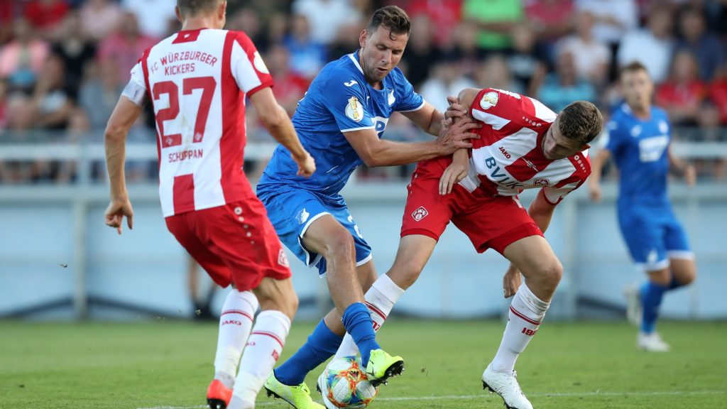 10 August 2019, Bavaria, Würzburg: Soccer: DFB Cup, Würzburger Kickers - 1899 Hoffenheim, 1st round in the Flyeralarm-Arena. Sebastian Schuppan (l) and Hendrik Hansen from Würzburg fight with Adam Szalai from Hoffenheim for the ball. Photo: Daniel Karmann/dpa - IMPORTANT NOTE: In accordance with the requirements of the DFL Deutsche Fußball Liga or the DFB Deutscher Fußball-Bund, it is prohibited to use or have used photographs taken in the stadium and/or the match in the form of sequence images and/or video-like photo sequences.