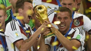 Germany's defender Kevin Grosskreutz (L) and Germany's forward Lukas Podolski hold up the World Cup trophy as they celebrate after winning the 2014 FIFA World Cup final football match between Germany and Argentina 1-0 following extra-time at the Maracana Stadium in Rio de Janeiro, Brazil, on July 13, 2014.  AFP PHOTO / FABRICE COFFRINI (Photo by FABRICE COFFRINI / AFP)