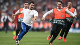Stewards run after a streaker during the UEFA Super Cup 2019 football match between FC Liverpool and FC Chelsea at Besiktas Park Stadium in Istanbul on August 14, 2019. (Photo by Bulent Kilic / AFP)