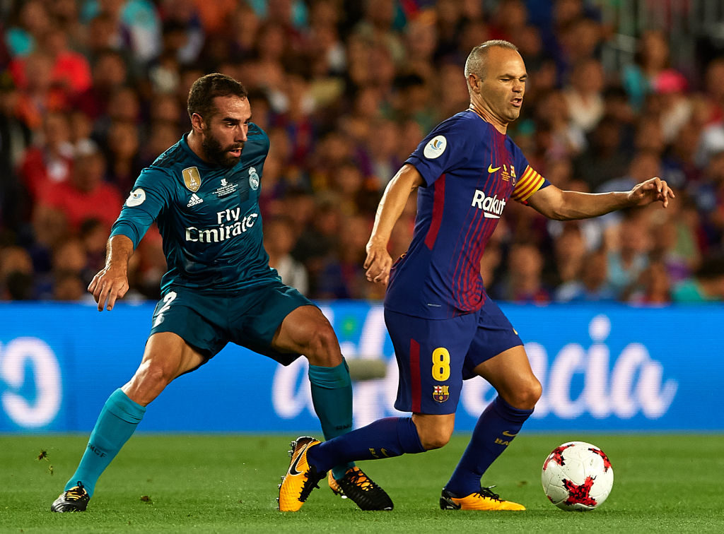 BARCELONA, SPAIN - AUGUST 13:  Andres Iniesta (R) of Barcelona is tackled by Daniel Carvajal of Real Madrid during the Supercopa de Espana Supercopa Final 1st Leg match between FC Barcelona and Real Madrid at Camp Nou on August 13, 2017 in Barcelona, Spain.  (Photo by Manuel Queimadelos Alonso/Getty Images,)