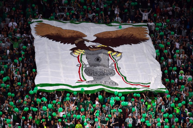 Fans of TC Frerencvaros display a banner of the Hungarian Cup with their symbol, an eagle, prior to the Hungarian Cup final football match between TC Ferencvaros and FC Ujpest at the Groupama Arena in Budapest on May 7, 2016. Ferencvaros won 1-0 and the Hungarian Cup.  / AFP PHOTO / ATTILA KISBENEDEK