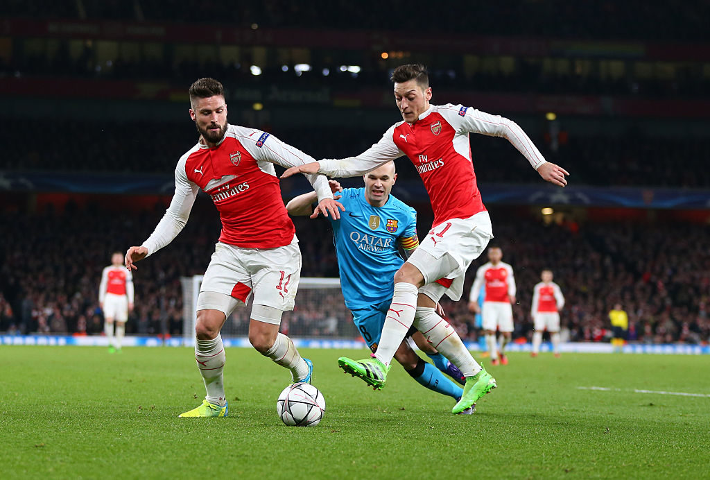 LONDON, ENGLAND - FEBRUARY 23 :  Andres Iniesta of FC Barcelona watches as Olivier Giroud and Mesut Ozil of Arsenal both go for the ball during the UEFA Champions League match between Arsenal and Barcelona at the Emirates Stadium on February 23, 2016 in London, United Kingdom.  (Photo by Catherine Ivill - AMA/Getty Images)