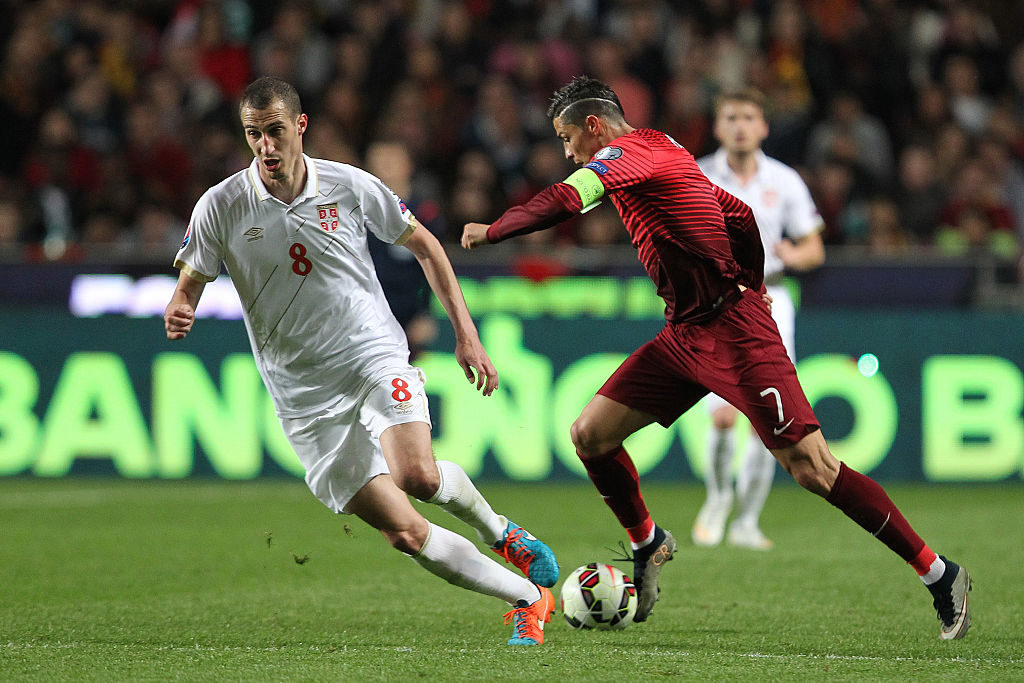 LISBON, PORTUGAL - MARCH 29:  Portugal's forward Cristiano Ronaldo pass trough Serbian'´s midfielder Radosav Petrovic during the UEFA Euro 2016 Qualifier between Portugal and Serbia at Estadio da Luz on March 29, 2015 in Lisbon, Portugal.  (Photo by Carlos Rodrigues/Getty Images)