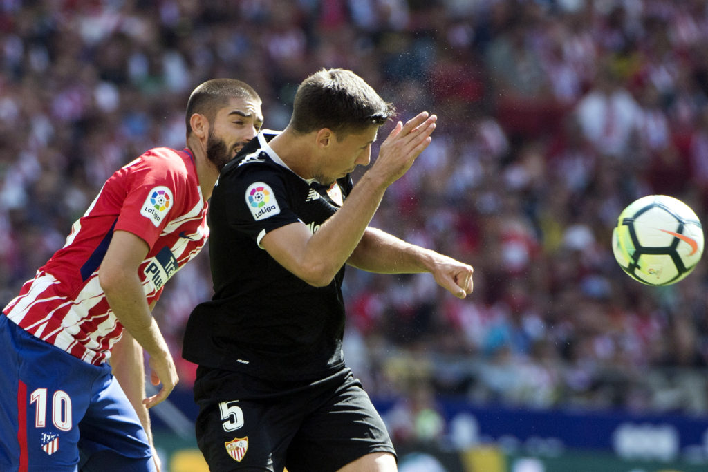 Atletico Madrid's midfielder from Belgium Yannick Ferreira-Carrasco (L) vies with Sevilla's defender from France Clement Lenglet during the Spanish league football match Club Atletico de Madrid vs Sevilla FC at the Wanda Metropolitano stadium in Madrid on September 23, 2017. / AFP PHOTO / CURTO DE LA TORRE