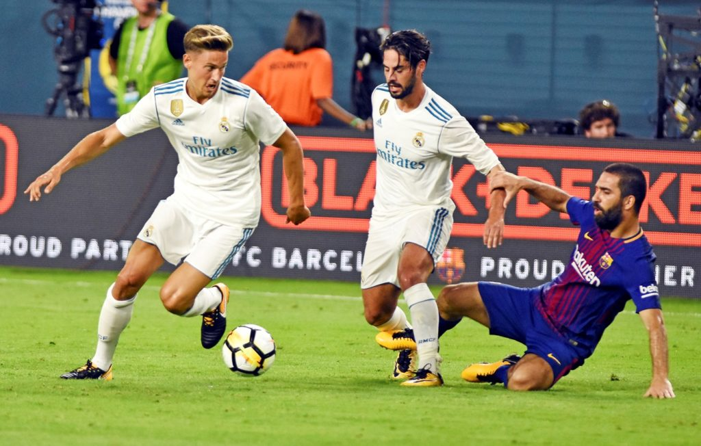 Madrid's Marcos Llorente and Isco fights for the ball against Real Madrid Arda Turna during the second half of the International Champions Cup soccer friendly at Hard Rock Stadium in Miami, Florida, on July 29, 2017.  Barcelona won 3-2. / AFP PHOTO / GASTON DE CARDENAS
