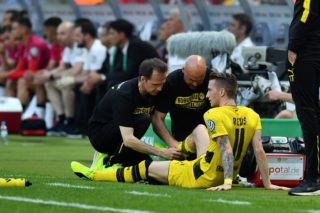 Dortmund's forward Marco Reus gets medical help as he is injured during the German Cup (DFB Pokal) final football match Eintracht Frankfurt v BVB Borussia Dortmund at the Olympic stadium in Berlin on May 27, 2017. Marco Reus' injury misery continues on May 29, 2017 when Borussia Dortmund confirmed the winger partially tore his cruciate ligament in Saturday's German Cup final - a set-back which could sideline him for months. / AFP PHOTO / Christof STACHE / Germany OUT / RESTRICTIONS: ACCORDING TO DFB RULES IMAGE SEQUENCES TO SIMULATE VIDEO IS NOT ALLOWED DURING MATCH TIME. MOBILE (MMS) USE IS NOT ALLOWED DURING AND FOR FURTHER TWO HOURS AFTER THE MATCH. == RESTRICTED TO EDITORIAL USE == FOR MORE INFORMATION CONTACT DFB DIRECTLY AT +49 69 67880 /