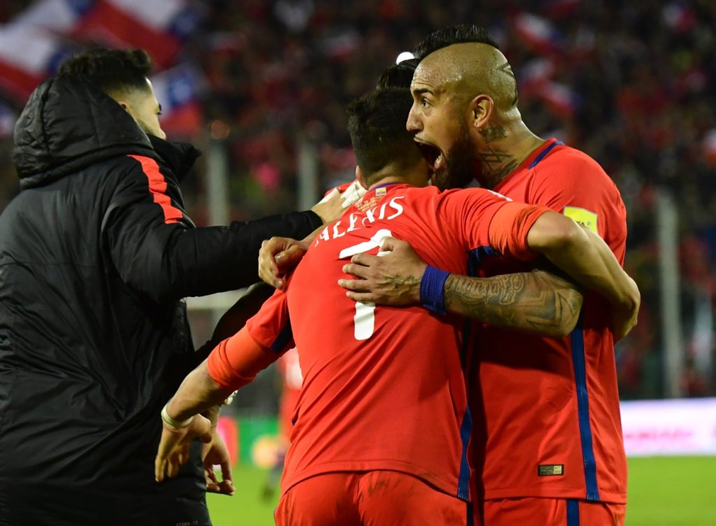 Chile's Alexis Sanchez (C) celebrates with teammate Arturo Vidal (R) after scoring against Ecuador during their 2018 World Cup qualifier football match in Santiago on October 5, 2017. / AFP PHOTO / Martin BERNETTI