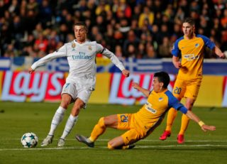 Real Madrid's Portuguese forward Cristiano Ronaldo (L) vies for the ball with Apoel's Greek defender Praxitelis Vouros (C) during the UEFA Champions League Group H match between Apoel FC and Real Madrid on November 21, 2017, in the Cypriot capital Nicosia's GSP Stadium.  / AFP PHOTO / Florian CHOBLET