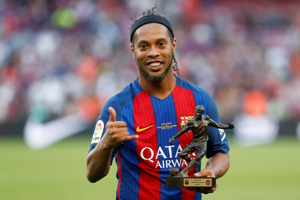 Former Barcelona's Brazilian forward Ronaldinho poses with the trophy for the best player after a charity football match between Barcelona Legends vs Manchester United Legends at the Camp Nou stadium in Barcelona on June 30, 2017. / AFP PHOTO / Pau Barrena