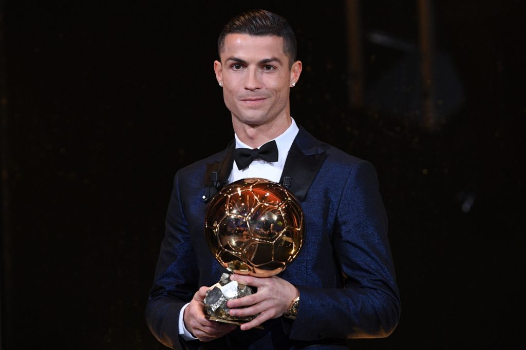 """This handout photo released on December 7, 2017 by L'Equipe shows Portugese player Cristiano Ronaldo posing with the 2017 Ballon d'Or France Football trophy in Paris. Portuguese star Cristiano Ronaldo won a record-equalling fifth Ballon d'Or (2008, 2013, 2015, 2016 and 2017) award for the year's best player on December 7. The Real Madrid forward's second successive win draws him level alongside Barcelona rival Lionel Messi on five Ballon d'Ors, after beating the Argentinian and Brazilian Neymar. / AFP PHOTO / L'EQUIPE / Franck FAUGERE / RESTRICTED TO EDITORIAL USE - MANDATORY CREDIT """"AFP PHOTO / L'EQUIPE / FRANCK FAUGERE"""" - NO MARKETING NO ADVERTISING CAMPAIGNS - DISTRIBUTED AS A SERVICE TO CLIENTS"""