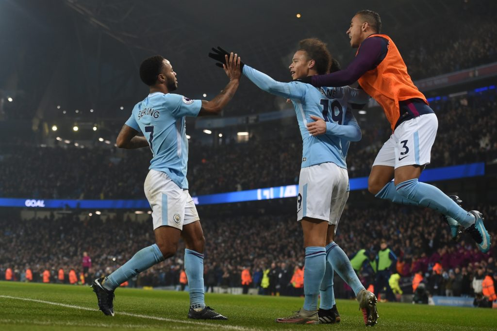 Manchester City's English midfielder Raheem Sterling (L) celebrates after scoring their third goal with Manchester City's German midfielder Leroy Sane during the English Premier League football match between Manchester City and Tottenham Hotspur at the Etihad Stadium in Manchester, north west England, on December 16, 2017. / AFP PHOTO / PAUL ELLIS / RESTRICTED TO EDITORIAL USE. No use with unauthorized audio, video, data, fixture lists, club/league logos or 'live' services. Online in-match use limited to 75 images, no video emulation. No use in betting, games or single club/league/player publications.  /