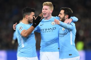 Manchester City's Argentinian forward Sergio Aguero (L) celebrates with Manchester City's Belgian midfielder Kevin De Bruyne (C) and Manchester City's Portuguese midfielder Bernardo Silva (R)  after scoring a goal  during the UEFA Champions League round of 16 first leg football match between Basel and Manchester City at the Saint Jakob-Park Stadium in Basel on February 13, 2018. / AFP PHOTO / SEBASTIEN BOZON