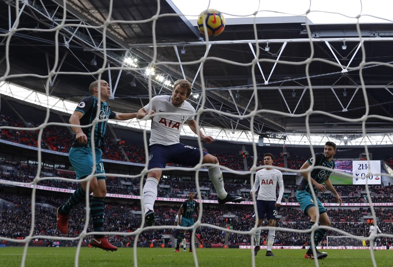 Tottenham Hotspur's English striker Harry Kane (3L) heads the ball to score the opening goal of the English Premier League football match between Tottenham Hotspur and Southampton at Wembley Stadium in London, on December 26, 2017. Harry Kane beat Alan Shearer's 36 goal record for the most Premier League goals scored in a calendar year, after scoring during Tottenham's game against Southampton. / AFP PHOTO / Adrian DENNIS / RESTRICTED TO EDITORIAL USE. No use with unauthorized audio, video, data, fixture lists, club/league logos or 'live' services. Online in-match use limited to 75 images, no video emulation. No use in betting, games or single club/league/player publications.  /