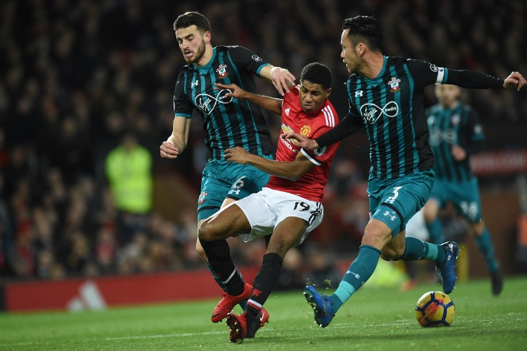Manchester United's English striker Marcus Rashford (C) vies with Southampton's Dutch defender Wesley Hoedt (L) and Southampton's Japanese defender Maya Yoshida (R) during the English Premier League football match between Manchester United and Southampton at Old Trafford in Manchester, north west England, on December 30, 2017. / AFP PHOTO / Oli SCARFF / RESTRICTED TO EDITORIAL USE. No use with unauthorized audio, video, data, fixture lists, club/league logos or 'live' services. Online in-match use limited to 75 images, no video emulation. No use in betting, games or single club/league/player publications.  /