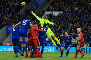 Huddersfield Town's Danish goalkeeper Jonas Lossl (C) punches the ball clear during the English Premier League football match between Leicester City and Huddersfield Town at King Power Stadium in Leicester, central England on January 1, 2018. / AFP PHOTO / Lindsey PARNABY / RESTRICTED TO EDITORIAL USE. No use with unauthorized audio, video, data, fixture lists, club/league logos or 'live' services. Online in-match use limited to 75 images, no video emulation. No use in betting, games or single club/league/player publications.  /