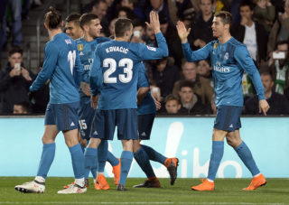 Real Madrid's French forward Real Madrid's Portuguese forward Cristiano Ronaldo (R) celebrates scoring a goal with teammates during the Spanish league football match Real Betis vs Real Madrid at the Benito Villamarin stadium in Sevilla on February 18, 2018. / AFP PHOTO / Cristina Quicler