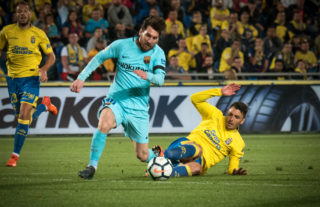 Barcelona's Argentinian forward Lionel Messi (R) vies Las Palmas' defender Ximo Navarro Jimenez (L) during the Spanish league football match UD Las Palmas vs FC Barcelona at the Gran Canaria stadium in Las Palmas de Gran Canaria on March 01, 2018. / AFP PHOTO / DESIREE MARTIN