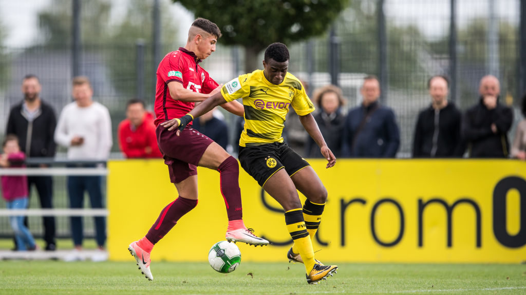 DORTMUND, GERMANY - AUGUST 19: Miran Agirbas (L) of Koeln and Youssoufa Moukoko (R) of Dortmund fight for the ball during the B Juniors Bundesliga match between Borussia Dortmund and FC Viktoria Koeln on August 19, 2017 in Dortmund, Germany. (Photo by Lukas Schulze/Bongarts/Getty Images)