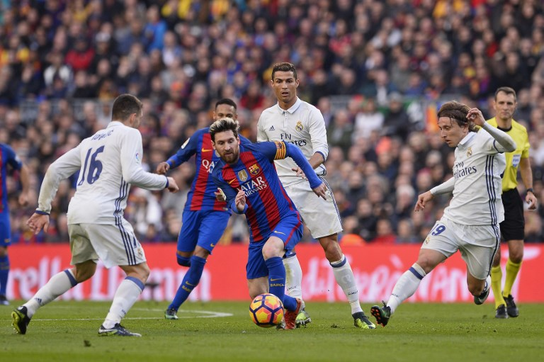 Barcelona's Argentinian forward Lionel Messi (C) vies with Real Madrid's Portuguese forward Cristiano Ronaldo (back) and Real Madrid's Croatian midfielder Luka Modric (R) during the Spanish league football match FC Barcelona vs Real Madrid CF at the Camp Nou stadium in Barcelona on December 3, 2016. / AFP PHOTO / JOSEP LAGO